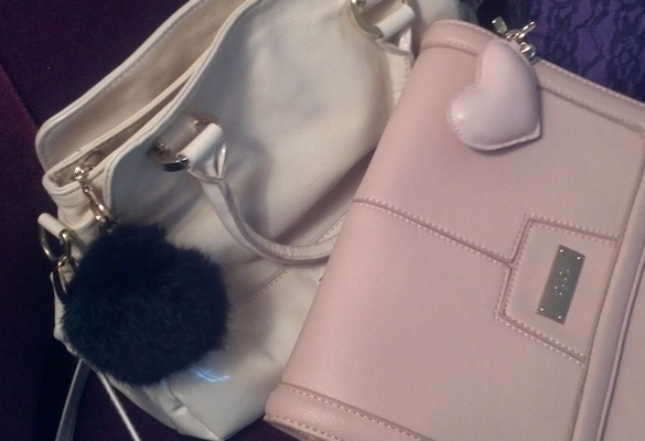 White leather purse with black charm, and pink BCBG purse with pink leather heart charm.