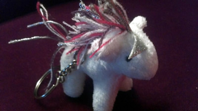 Adorable unicorn purse charm with bent silver horn.
