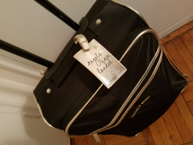 """Black suitcase with """"Angels have landed"""" tag."""
