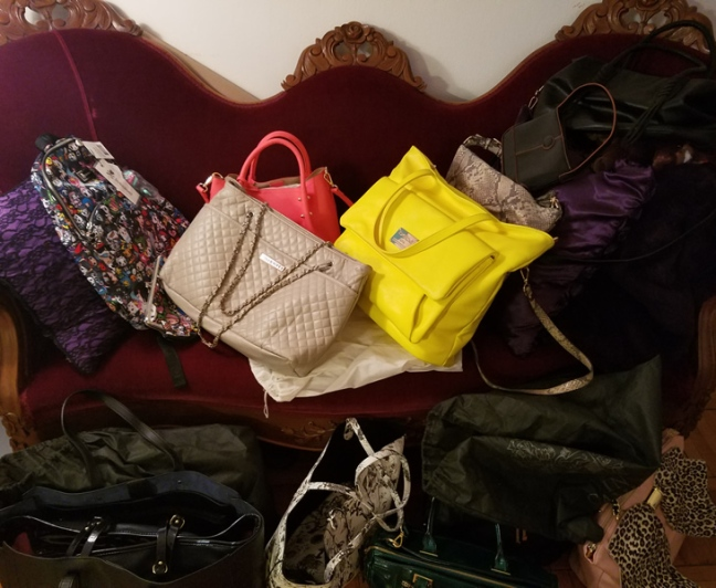 Many brightly colored purses piled up on sofa.