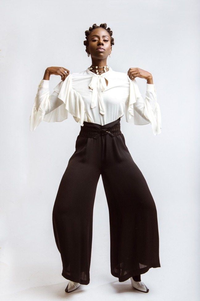 Model wearing lovely white shirt and high waist, wide-leg black pants