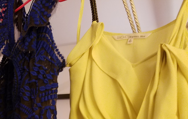 Blue embroidered mesh dress hanging beside yellow Rachel Roy dress with chain strap