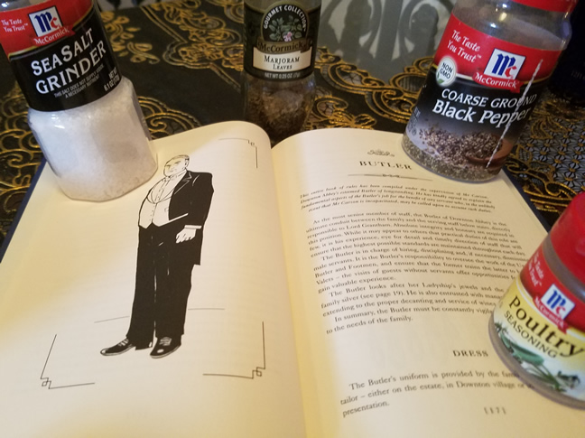 Sea salt, marjoram, black pepper and poultry seasoning holding down a book with picture of butler Mr. Bates