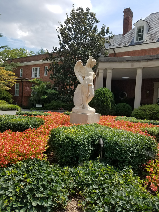 White statue of Cupid, reaching into his quiver of arrows. He stands among vines, bushes and red flowers, all shaped like radiating arrows.
