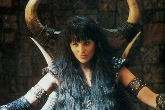 Xena, seated on a throne of bones and hide, looking badass.